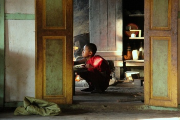 little monk eating dinner at the monastery next door