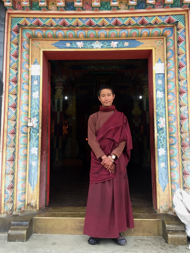 A Tibetan monk stands in front of his temple in Upper Pisang