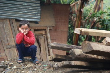A boy squats on the wreckage of his school. His ''this sucks'' expression says it all. Local carpenters were able to construct four new classrooms with the building supplies and funding we provided