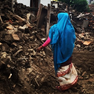 a grandmother walks through the rubble that used to be her home in a village outside Kahmandu