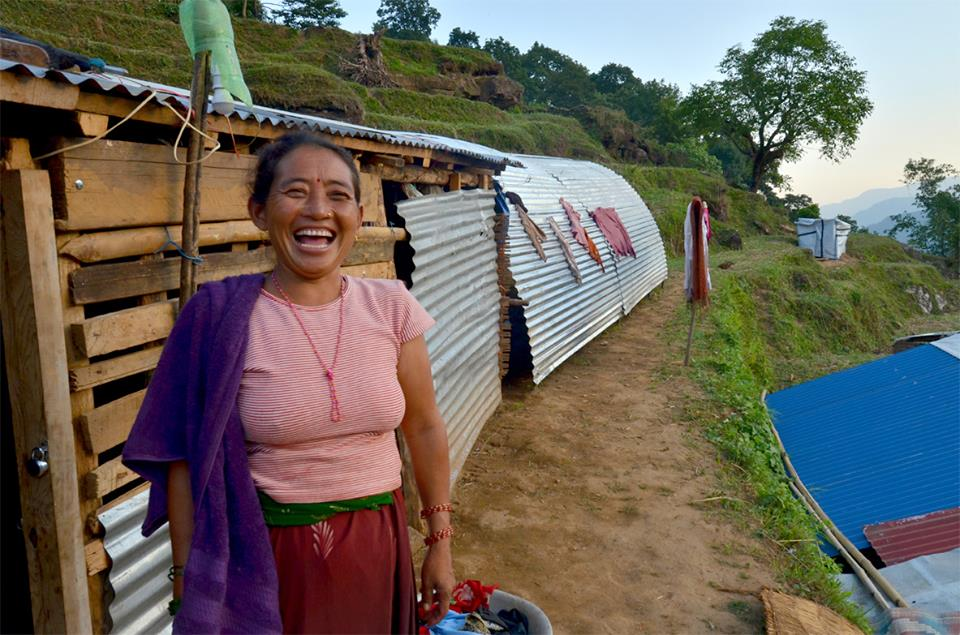 a women smiles next to her new shelter in a remote village in Gorhka (photo credit: Karma Flights)