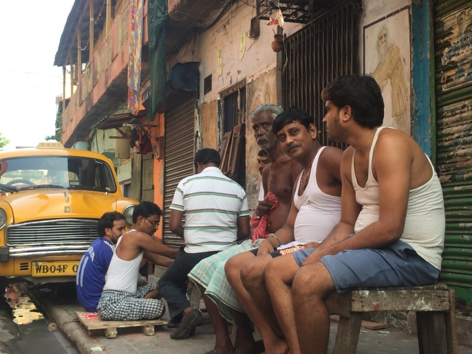 Neighborhood in north Calcutta- men sitting by a chai stand, behind - playing cards on the sidewalk.